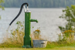 Water pump in front of a lake in summertime