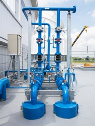 Water pump station and water cooling tower on roof deck of water tank. Including with electric motor, pipeline, valve control and electrical control box for water cooling system of industry process.