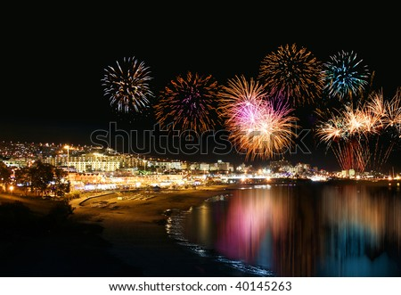 Water reflecting night fireworks in seashore holiday resort festive