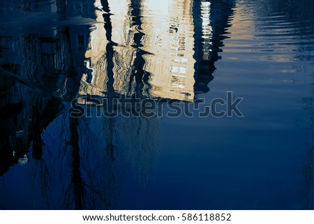 Water reflection home in the puddle. Apartment building is reflected in the spring floods with a blue sky and the bare trees without leaves. The forms of objects and plants distorted. #586118852