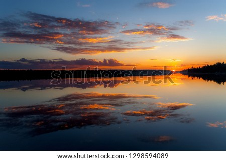 water reflections at midnight sun at lake inari in finland, scandinavia, europe #1298594089