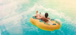 Water resort with waterslide and swimming pool for water adventure on vacation, cool people having fun in waterpark. Travel on summer for recreation in the pool. Beach party for cool people on holiday