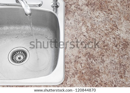 Water running from kitchen faucet. Clean new sink and countertop detail.