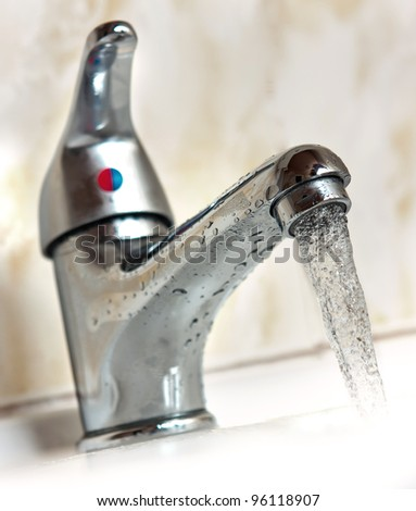 Water running from metal tap. Shallow depth of field