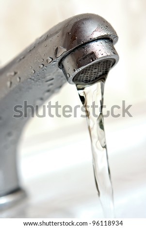 Water running from tap. Macro, shallow depth of field