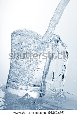 water running into a glass isolated on white