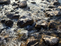 Water running through rocks in a shallow stream. This is actually water flowing from a glacier in the Fann mountains in Central Asia. Freshwater, cold and bubbly with some foam on rocks. Very natural.