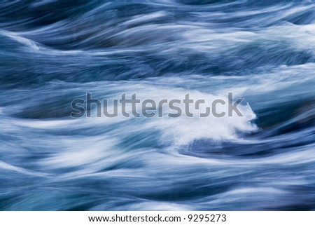 Water rushing by in river forming a painted appearing abstract pattern.