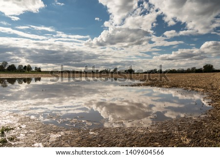 Water soaked field with clouds reflected in the flood waters. Standing water prevents planting, threatens the harvest & the livelihood of family farms. Concepts of crop insurance & climate change.