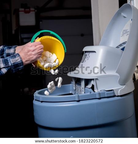 Water softener maintenance adding more salt when needed Foto stock ©