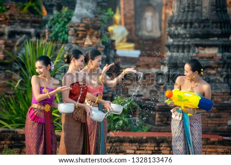 Water Songkran festival. Asia young woman wearing Thai traditional costume play water in Songkran day water festival of Thailand. Women group using water gun and bolw play in the temple.  Culture Thai