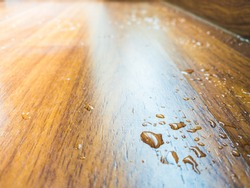 water spill on parquet wood floor, which leaking from air conditioner in the house.