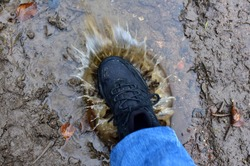 Water splash from shoes. Men's feet in hiking shoes steps into a puddle. Rain footwear for man or woman. Trekker boots for for cold and weather hike. Pair of waterproof travel shoe in blue jeans.