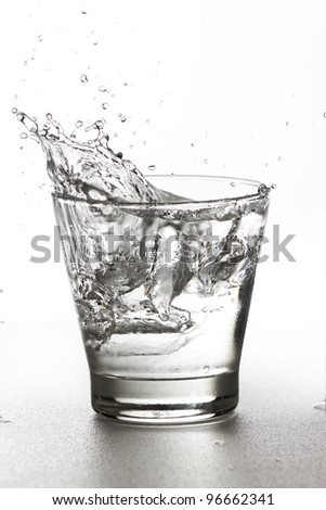 Water splash in glass isolated on white background.