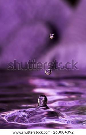 Water splash with two falling drops on dark purple background.