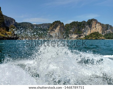 Water splashed occur after the boat runs in the turquoise sea.The turquoise sea has mountains and bright skies as background images. #1468789751