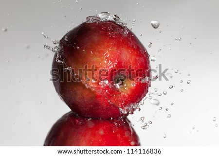 Water splashes on the apple.