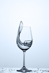 Water splashing from wineglass with cleaner water while standing on the glass with droplets against light background.