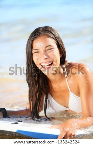 Water sport fun - beach woman bodyboarding surfing on bodyboard or boogieboard. Girl laughing having fun during summer holidays vacation travel. Lifestyle image mixed race Asian Caucasian female model