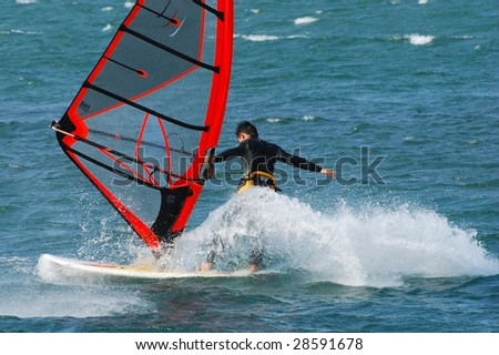water sports: windsurfer with bright colored sail on taiwan blue water