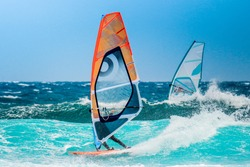water sports: windsurfers with colored sails in oceanic blue water