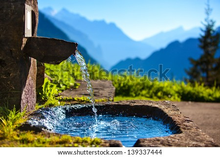 Water spring on Alps mountains background. #139337444