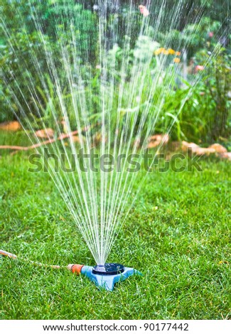 Water sprinkler. Irrigation system - technique of watering in the garden. Lawn sprinkler spraying water over green grass.