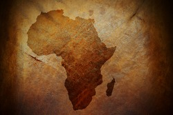 Water stain mark in the shape of the Africa continent map on a weathered brown leather parchment.