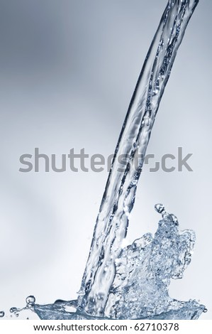 Water stream and splash over blue background - stock photo