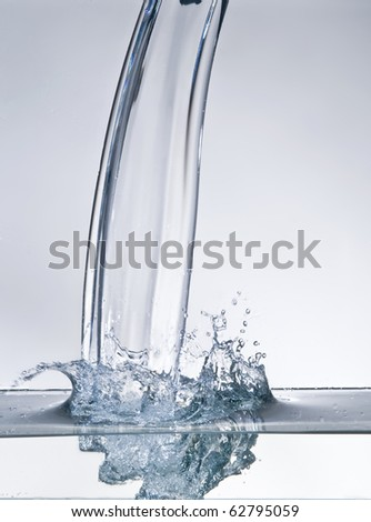 Water stream and splash over blue background