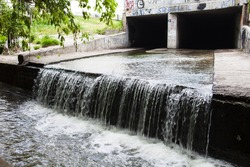 Water stream flowing out the underground tunnel into the Lybid river in Kyiv.