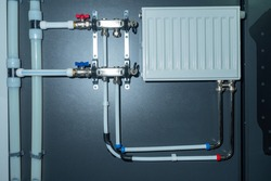 Water supply and heating. The pipe system is connected to the battery. Pipes, fittings, valves, battery on a gray wall. Demonstration of water supply components.