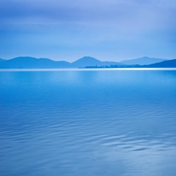 Water surface in a blue morning on the Trasimeno lake, Umbria Italy. Hills on background. Long exposure photography in Lido Camaiore, Versilia, Tuscany, Italy, Europe
