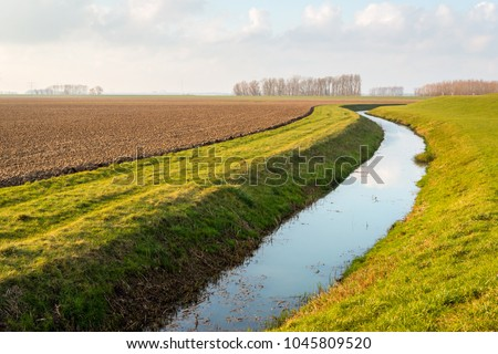 Water surface of a meandering ditch reflects the white clouds in the blue sky. The field next to the ditch has recently been plowed in preparation for the new growing season.