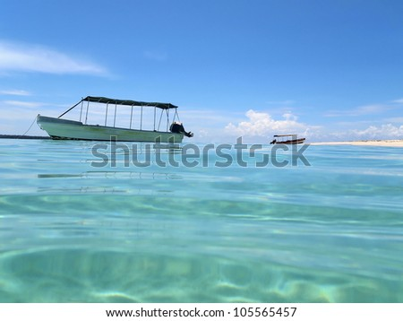 Water surface ripples with a boat anchored and sandy beach, Caribbean sea, Zapatilla island, Panama