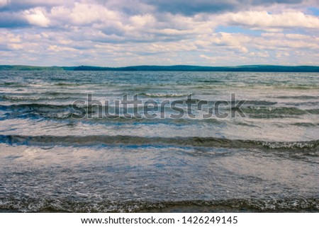 Water surface. View of a summer sky background. Dramatic cloudy sky with heavy clouds over the lake. View of a lake water texture. Landscape. Small waves. #1426249145