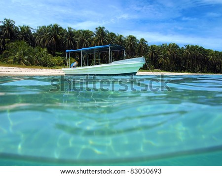 Water surface with boat anchored near tropical island beach in the Caribbean sea, Bocas del Toro, Zapatillas islands, Panama