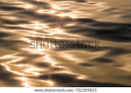 Water surface with moving wave of golden water reflecting sunlight