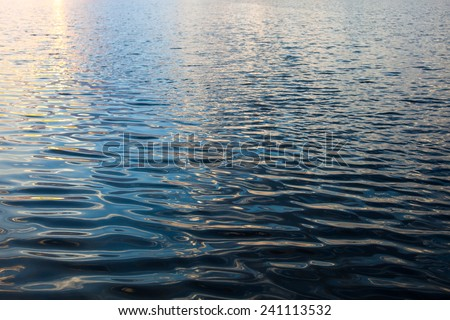 Water surface with ripples and sunrays reflections #241113532