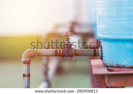 water tank with old metal valve....