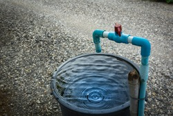 Water tap. Blue tube faucet and the red shutter valve, which is now open, drops water onto the black tank The water tank must be covered with water tap to save and conserve the environment