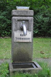 water tap in a concrete cemetery on the lawn