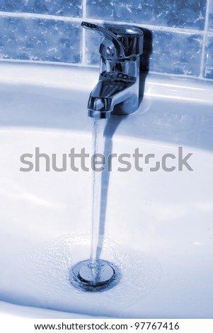 Water tap with a water stream. Blue tone image