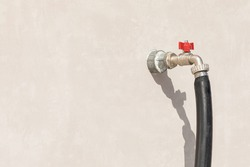 Water tap with red valve and hose, from outer, street wall of building, house. Equipment for watering lawns and flower beds, plant care.