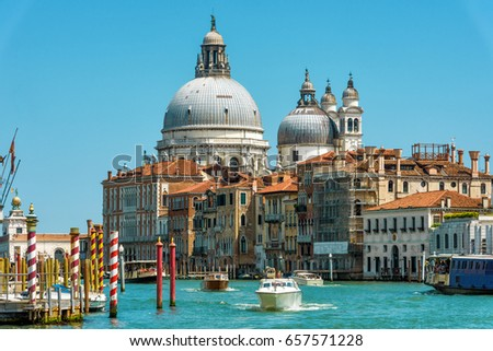 Water taxis and other tourist boats sail on the Grand Canal, Venice, Italy. Motor boats are the main transport in Venice. Nice panorama of Venice in summer. Romantic marine trip across sunny Venice. #657571228