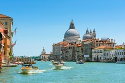 Water taxis are sailing on the Grand Canal, Venice, Italy. Sunny panoramic view of Venice with boats. Motorboats are the main transport in Venice. Panorama of the main street of Venice in summer.