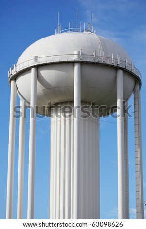 Water tower painted in white against blue sky