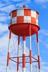 Water tower with red and white stripes (blue sky background)