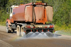 Water Truck Spraying Gravel Road to Suppress Dust and Prepare for Asphalting