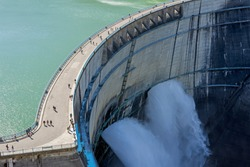 Water Turbines Are Producing Electricity At Power Plant. Panorama View Of Hydro Power Station And People On Kurobe Lake Dam,Toyama. River Dam and Tateyama Mountains.